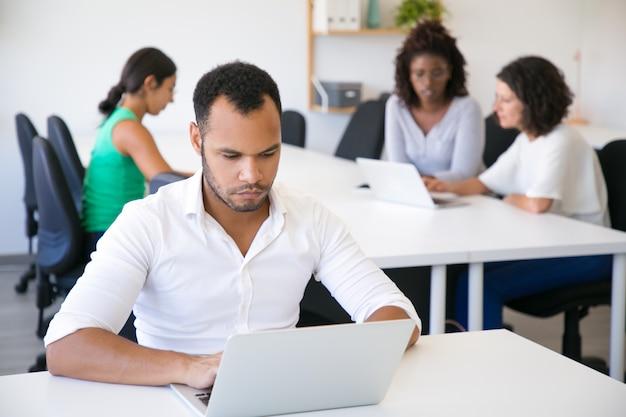 Poważny lider biznesu działa na laptopie