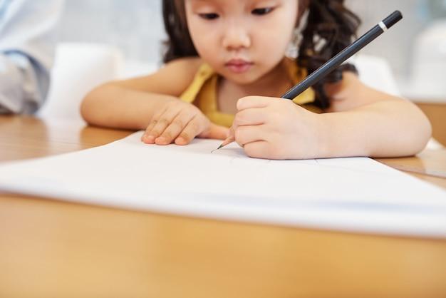 Poważny mały azjatycki rysunek ołówkiem na białej kartce, selektywne focus