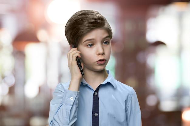 Poważny mały chłopiec rozmawia przez telefon