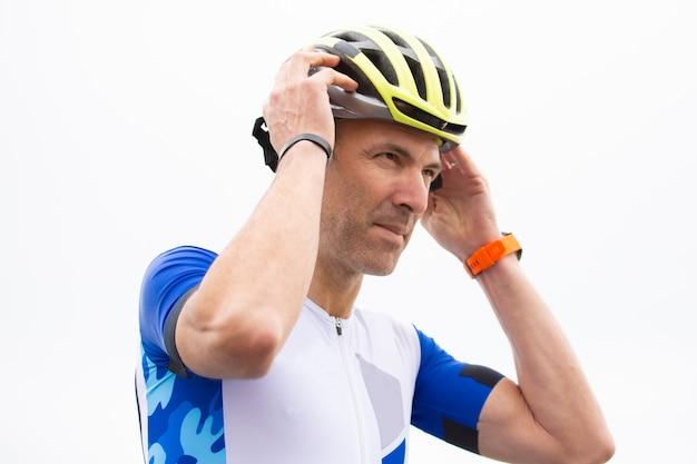 Poważny męski cyklista jest ubranym hełm