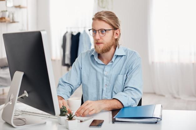 Poważny męski handlowiec o blond włosach, brodzie, okularach i niebieskiej koszuli, przygotowuje raport finansowy o dochodach firmy, pisząc na klawiaturze komputera, siedzi przeciwko nowoczesnemu lekkiemu biurowemu wnętrzu.