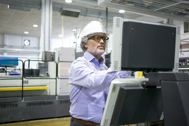 Poważny męski kierownik zakładu w kasku i okularach obsługujący maszynę przemysłową, wciskający przyciski na panelu sterowania