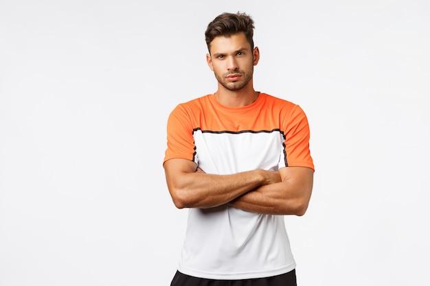 Poważny męski mężczyzna z włosiem, nosi sportowy t-shirt, skrzyżowane ramiona na piersi.