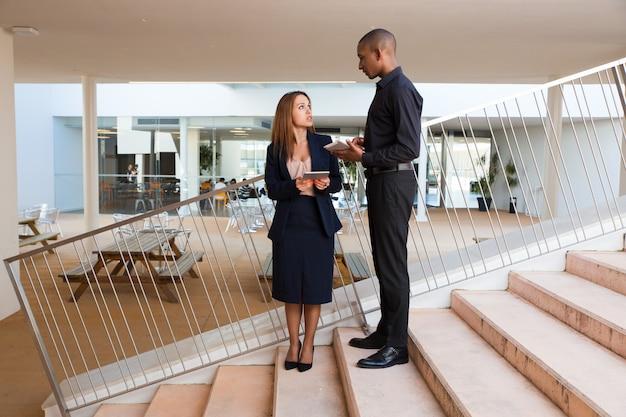 Poważny męski szef instruuje żeńskiego asystenta