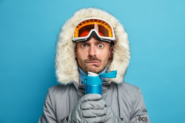 Poważny mężczyzna drży z zimna po wyjściu na narty w mroźny, zimowy dzień trzyma termos z gorącym napojem, nosi gogle narciarskie i ciepłą kurtkę.