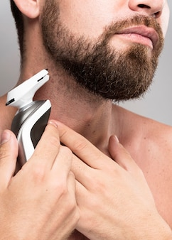 Poważny mężczyzna goli brodę