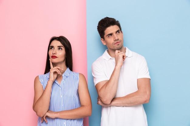 Poważny mężczyzna i kobieta w casual dotykając podbródków i patrząc na bok, na białym tle nad kolorową ścianą