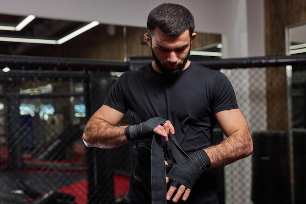 Poważny mężczyzna kickboxer fighter przygotowuje się do walki, owija rękę w bandaż, przygotowuje się, idzie na trening i ćwiczy