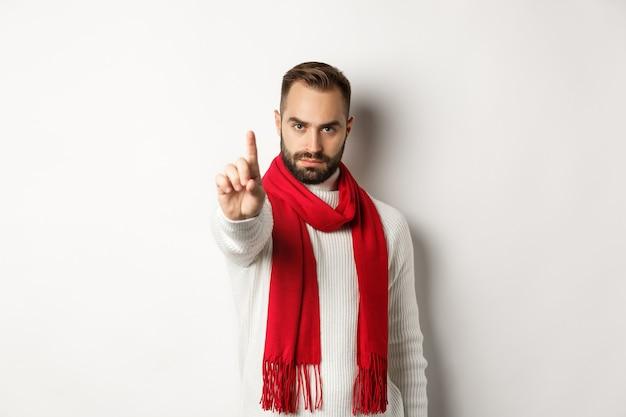 Poważny mężczyzna mówiący nie, pokazujący znak stopu, potrząsający palcem w dół, znak odrzucenia, zakazujący działania, stojący w zimowym swetrze i czerwonym szaliku na białym tle
