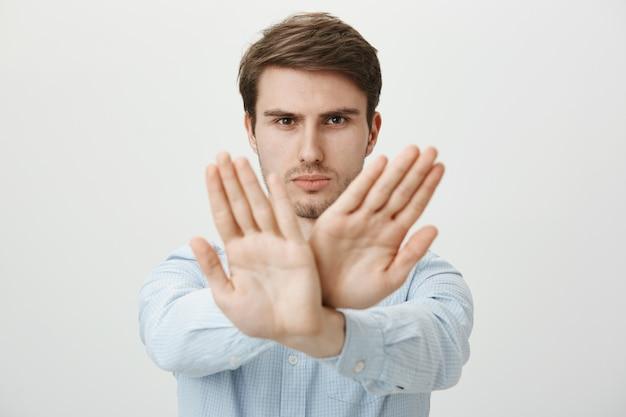 Poważny mężczyzna pokazujący gest zatrzymania, ograniczenia lub zakazu działania