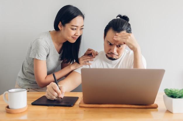 Poważny mężczyzna pracuje ze wsparciem żony