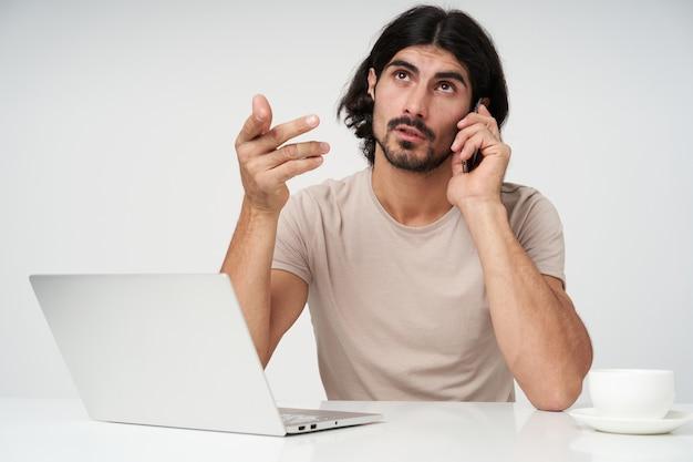 Poważny mężczyzna, przystojny biznesmen z czarnymi włosami i brodą. koncepcja biura. rozmawiaj przez telefon. radzenie sobie z klientami. siedząc w miejscu pracy, odizolowane z bliska na białej ścianie