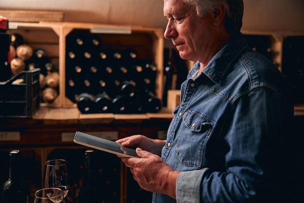 Poważny mężczyzna robotnik winnicy stojący w piwnicy z tabletem w ręku. półki z butelkami wina w tle