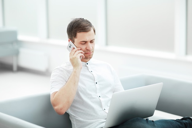 Poważny mężczyzna rozmawiający przez telefon, siedzący w holu hotelu