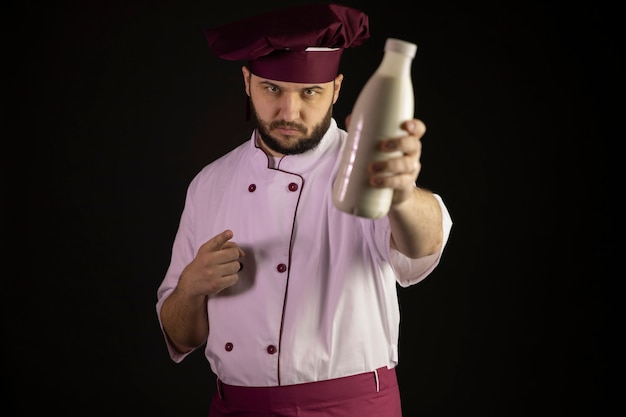 Poważny mężczyzna szefa kuchni w mundurze trzyma butelkę mleka, koncentruje się na kitchener