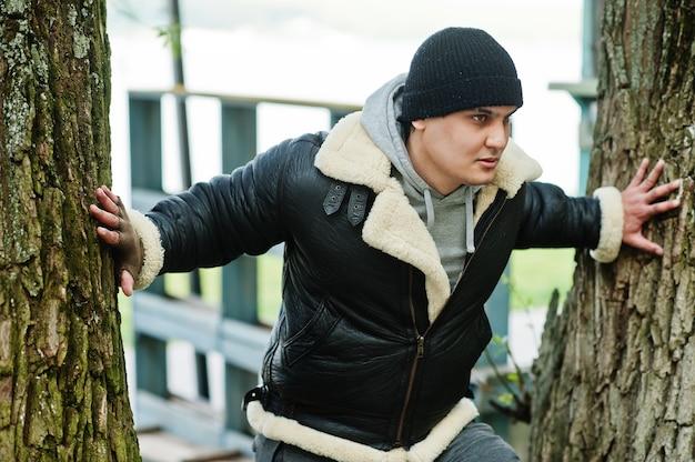 Poważny mężczyzna ubrany w skórzaną kurtkę i czarny kapelusz
