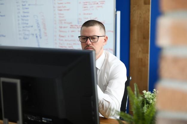 Poważny mężczyzna w okularach i koszuli siedzieć i patrzeć na monitor komputera.