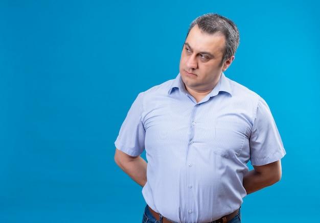 Poważny mężczyzna w średnim wieku w myśli w niebieskie paski koszuli kładzie ręce na plecach na niebieskim tle