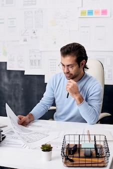 Poważny mężczyzna w średnim wieku w okularach siedzi przy biurku i ogląda szkice, myśląc o projekcie interfejsu użytkownika