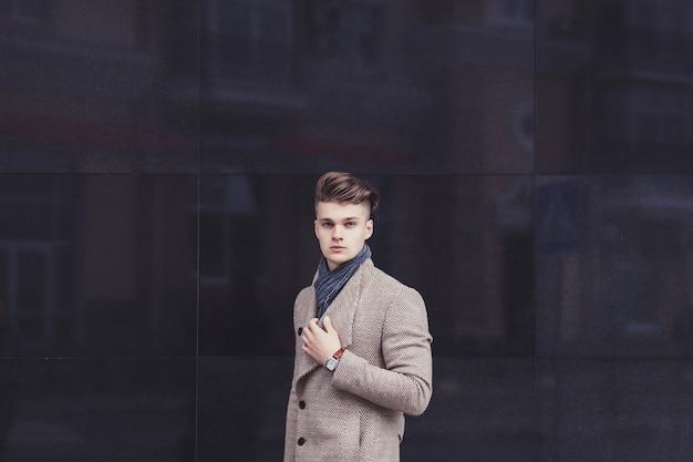 Poważny mężczyzna w stylowym płaszczu na ścianie