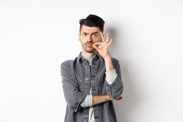 Poważny mężczyzna wykonujący gest zamka, mówi, żeby trzymał usta na kłódkę, marszczy brwi i pieczętuje usta, stojąc na białym tle.