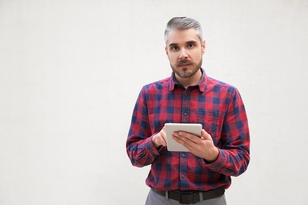 Poważny mężczyzna z cyfrowy tablicowy patrzeć