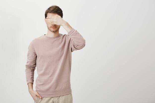 Poważny mężczyzna zasłania oczy, stoi z zawiązanymi oczami