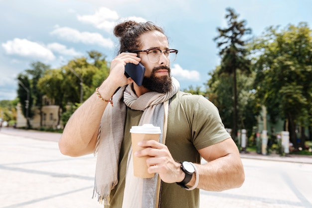 Poważny miły człowiek przykłada telefon do ucha podczas rozmowy telefonicznej