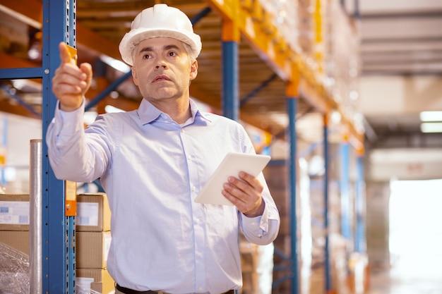 Poważny miły człowiek trzymający tablet podczas pracy