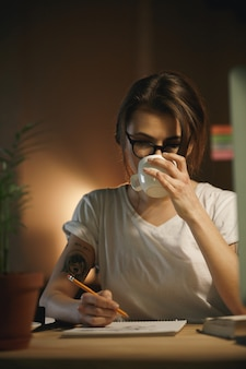 Poważny młoda kobieta projektant pisze notatki i pije kawę