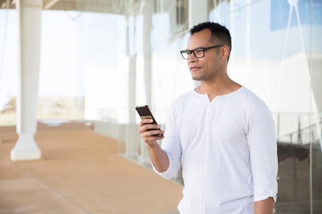 Poważny młodego człowieka mienia telefon w rękach, patrzeje na boku