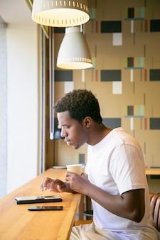 Poważny młody afroamerykanin pije kawę siedząc przy biurku w przestrzeni coworkingowej, za pomocą tabletu, pisania i czytania na ekranie