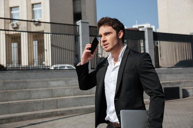 Poważny młody biznesmen chodzi outdoors opowiadać telefonem.