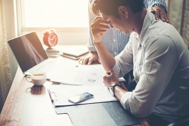 Poważny młody biznesmen, patrząc na sprawozdanie finansowe wyglądać