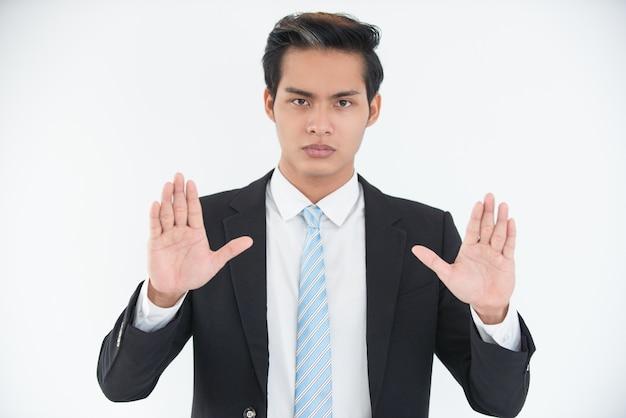 Poważny młody biznesmen pokazano otwarte palmy