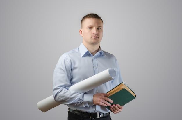 Poważny młody biznesmen posiadający plany i architekt książki. na białej powierzchni