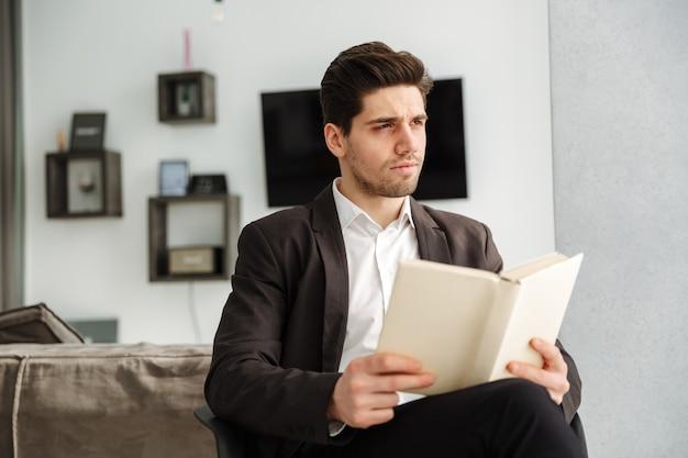 Poważny młody biznesmen siedzi w domu