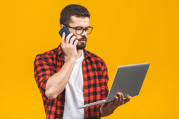 Poważny młody biznesowy mężczyzna w przypadkowy z laptopu obsiadaniem przy podłoga dzwoni z mądrze telefonem.