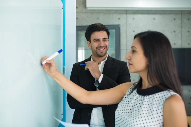 Poważny młody bizneswomanu rysunek na whiteboard