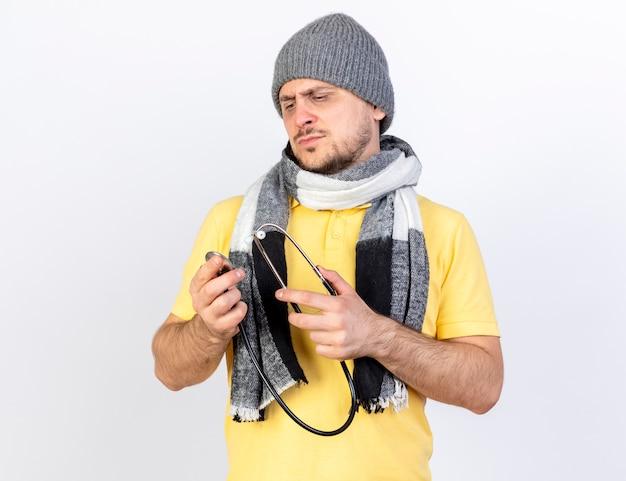 Poważny młody blondyn chory ubrany w czapkę zimową i szalik trzyma i patrzy na stetoskop na białym tle na białej ścianie