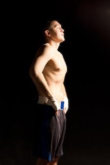 Poważny młody bokser nakręcający się przed walką w ciemności