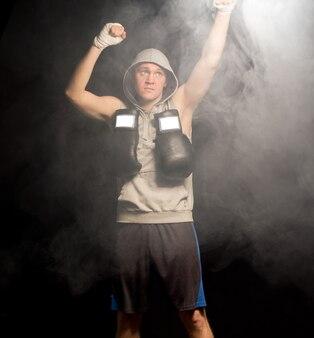Poważny młody bokser podnoszący wysoko pięści