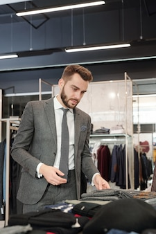 Poważny młody brodaty biznesmen z serwetką w kieszeni kurtki dotykając tkaniny ubrań podczas wybierania odzieży w sklepie