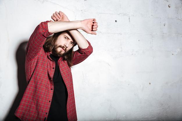 Poważny młody brodaty hipster mężczyzna w kapeluszu ubrany w koszulę w klatce odizolowanej nad ścianą, patrząc na przód