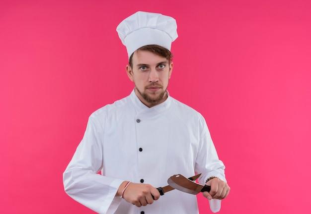 Poważny młody brodaty mężczyzna kucharz w białym mundurze na sobie nóż szefa kuchni do ostrzenia, patrząc na różową ścianę