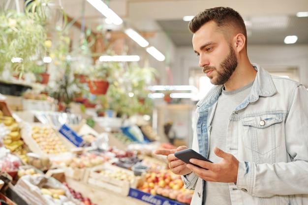 Poważny młody brodaty mężczyzna w kurtce stojący przy ladzie z jedzeniem i sprawdzający listę zakupów za pośrednictwem aplikacji na smartfona