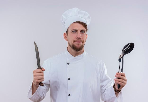 Poważny młody brodaty szef kuchni ubrany w biały mundur kuchenki i kapelusz, trzymając nóż, widelec i chochlę, patrząc na białej ścianie