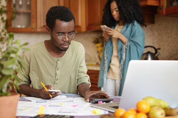 Poważny, młody, ciemnoskóry mężczyzna w okularach, korzystający z telefonu komórkowego i kalkulatora podczas obliczania wydatków rodzinnych