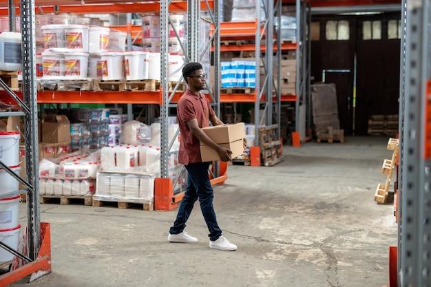 Poważny młody czarny facet w stroju codziennym niosący kartony w hipermarkecie magazynowym lub sprzętowym