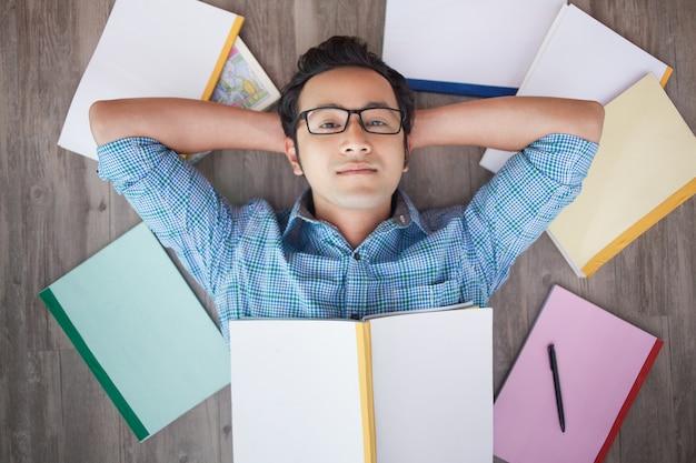 Poważny młody człowiek azji relaks na podłodze z książek